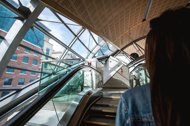Femme sur les escalators à la station de métro