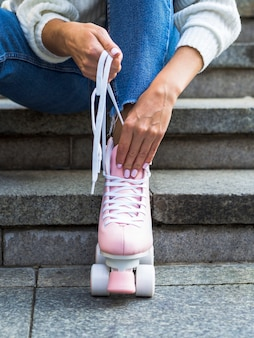 Femme, escalier, réparation, lacets, patins a roulettes