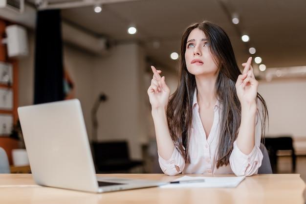 Femme espérant et tenant les doigts croisés dans le bureau