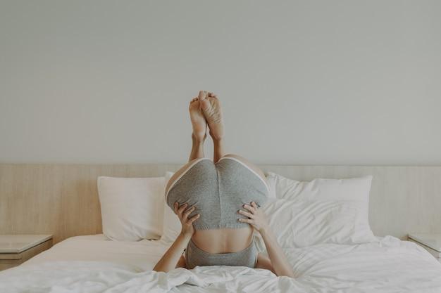 La femme espiègle fait la pose à l'envers sur le lit