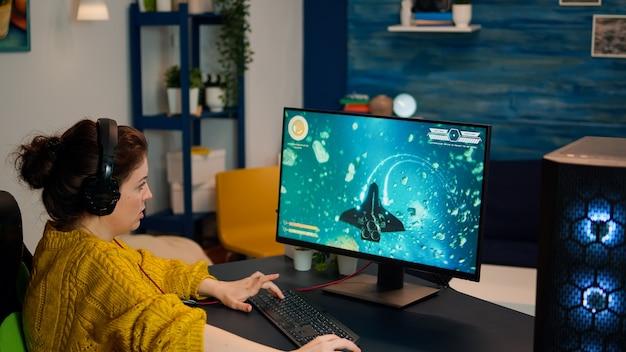 Femme esports professionnelle jouant à des jeux vidéo sur un pc puissant et moderne. jeune joueur professionnel jouant à un jeu de tir se produisant sur un ordinateur dans une pièce élégante pendant un tournoi de jeu