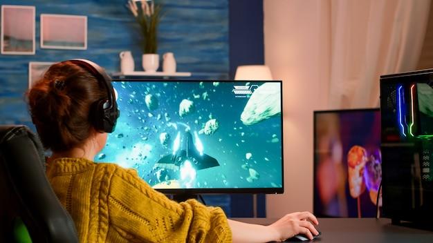 Femme esports professionnelle jouant à des jeux vidéo sur un pc puissant et moderne