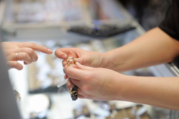 Femme essayant des alliances chez un bijoutier, se concentrant sur la bague