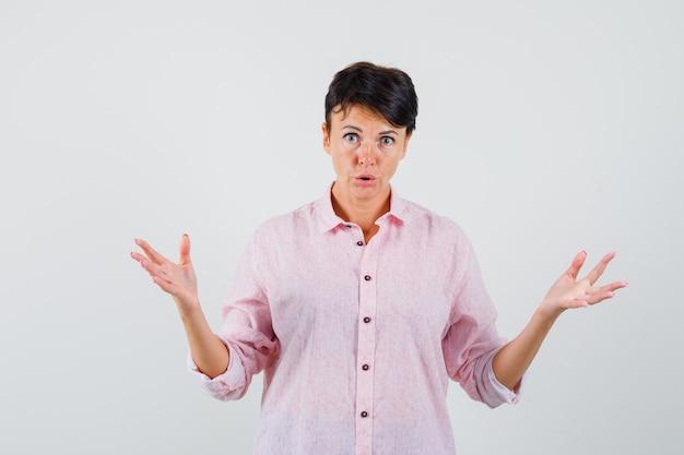 Femme essayant de clarifier le problème en chemise rose et à la confusion, vue de face.