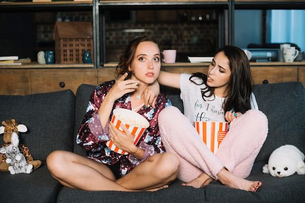 Femme essayant de prendre du pop-corn dans le seau de son amie tout en regardant la télévision