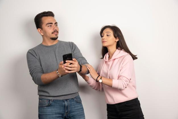 Femme essayant de regarder dans son téléphone sur blanc.