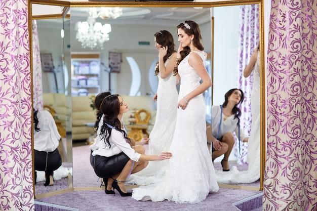 Femme essayant la robe de mariée dans un magasin avec une assistante féminine.