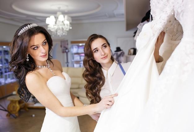 Femme essayant une robe de mariée dans un magasin avec une assistante féminine.