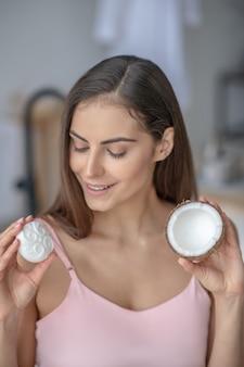 Femme essayant un savon avec une huile de noix de coco