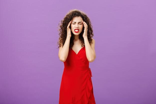Femme essayant de se concentrer et de rassembler ses pensées se sentant obligée de tenir les doigts sur les tempes en grimaçant et en serrant les dents en fermant les yeux debout avec une migraine et des maux de tête sur fond violet.