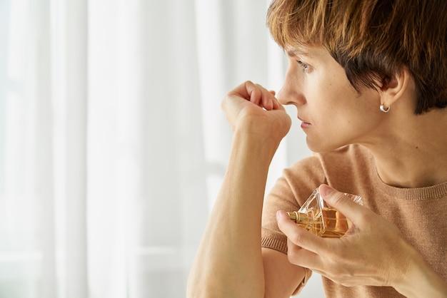 Femme essayant de sentir la perte d'odeur d'une bouteille de parfum en raison du syndrome du long covid du sarscov