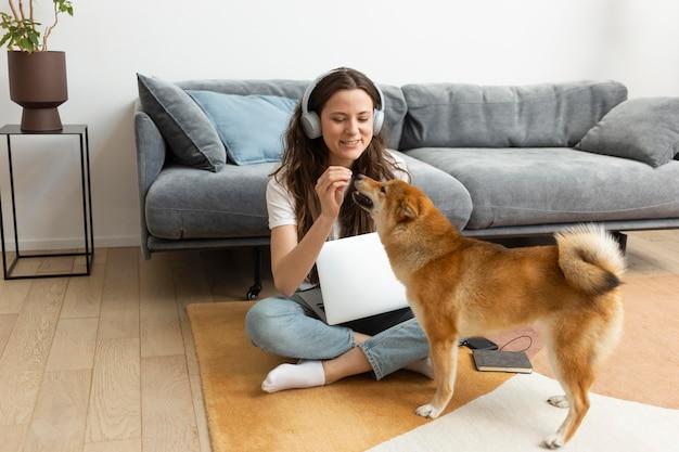 Femme essayant de travailler avec son chien autour