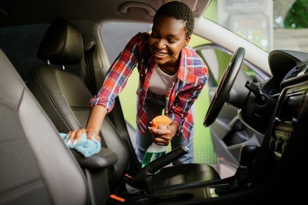 Une femme essuie l'intérieur de la voiture avec un chiffon, un lavage automatique à la main
