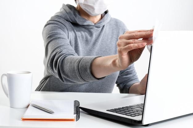 Femme essuie un ordinateur avec une lingette antibactérienne