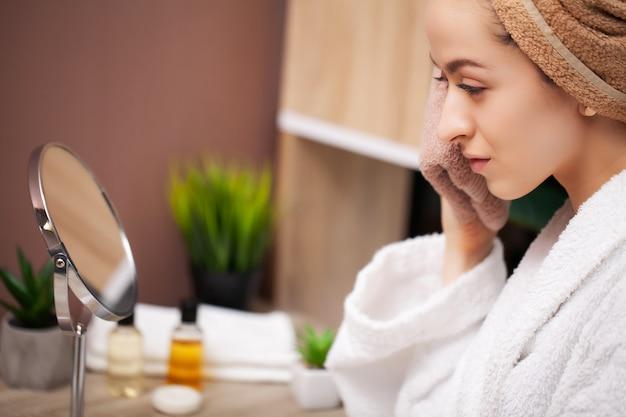 Femme essuie la serviette du visage après avoir pris une douche