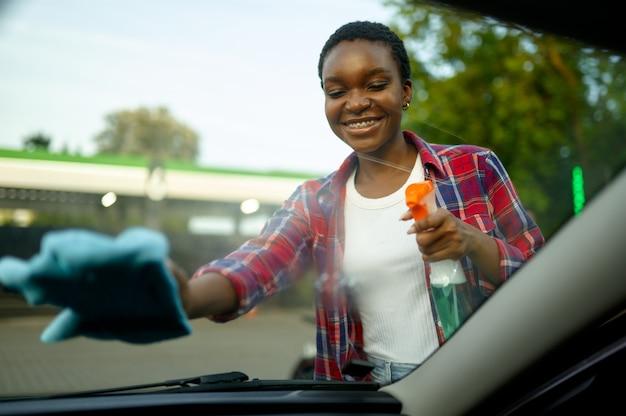 Femme essuie la vitre de la voiture avec un chiffon, lavage automatique à la main