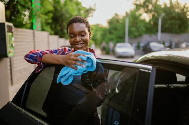 Une femme essuie une voiture avec un chiffon, une station de lavage automatique des mains. industrie ou entreprise de lavage de voitures. la personne de sexe féminin nettoie son véhicule à l'extérieur