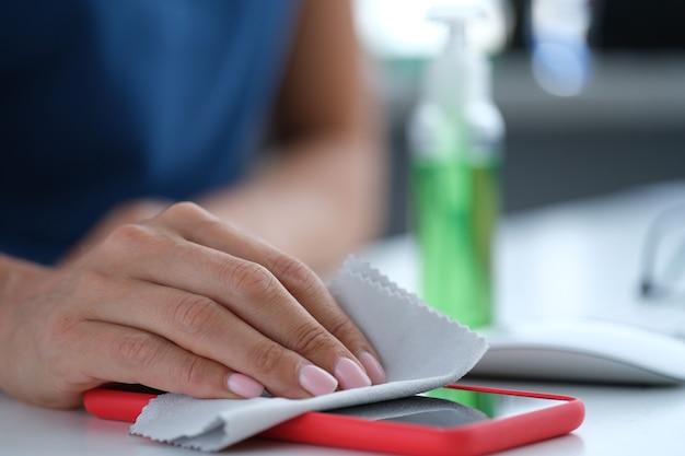 Femme essuyant l'écran du téléphone portable avec une serviette antiseptique en gros plan