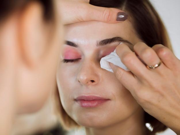 Femme essuyant le maquillage des yeux du modèle
