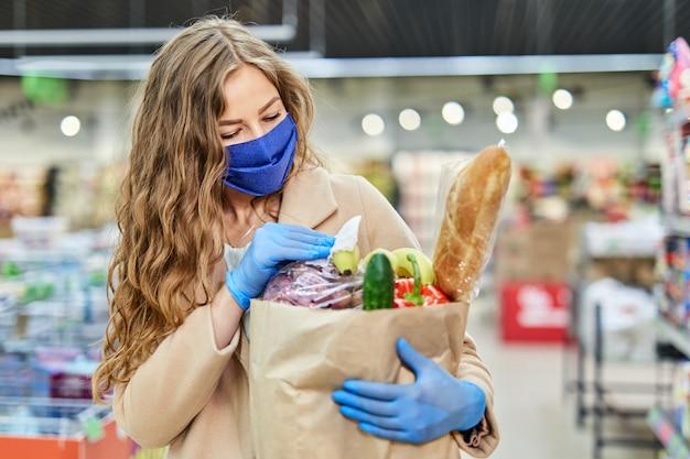 Femme essuyant les paquets d'épicerie avec des gants, à l'aide de lingettes désinfectantes ou désinfectantes