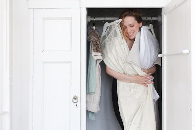 Une femme est accablée dans un placard de vêtements en désordre