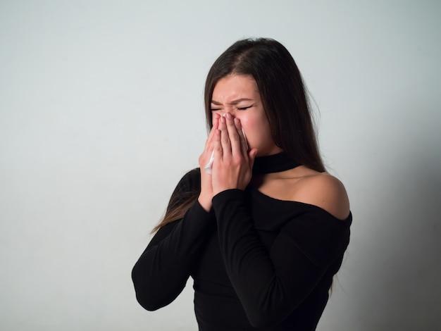 La femme est allergique. femme en pull noir sur mur blanc