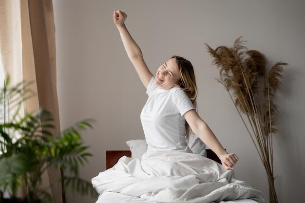 Une femme est allongée dans son lit après une bonne nuit de sommeil. grand réveil et début d'une nouvelle journée. reposez-vous la nuit.