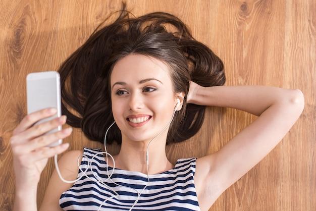La femme est allongée sur le sol et écoute de la musique.
