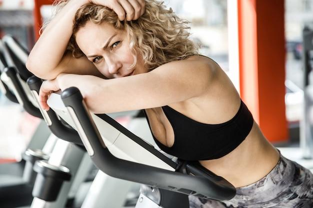 Une femme est allongée sur un vélo d'exercice de près. elle regarde la caméra.