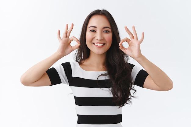 Une femme est-asiatique brune agréable et joyeuse satisfaite en t-shirt rayé garde tout sous contrôle, accepte ou approuve quelque chose de génial, montre des signes d'accord, hoche la tête en accord et sourit