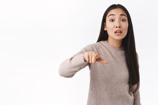 Femme est-asiatique outrée et furieuse menaçant quelqu'un, pointant la caméra du doigt ayant un argument, blâmant ou accuse une personne, étant grossière, criant, avertissant quelqu'un, debout énervé sur un mur blanc