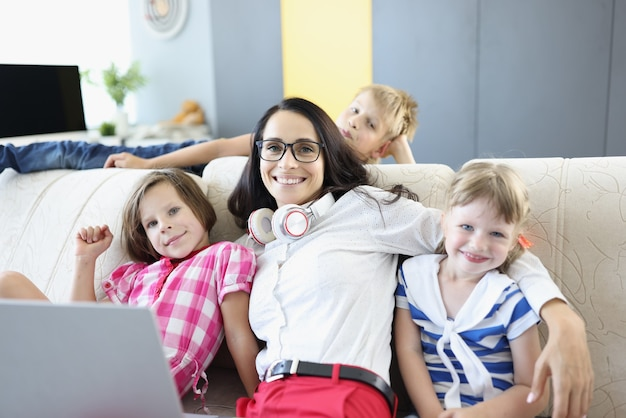 La femme est assise sur un canapé avec deux filles et le garçon est debout à côté de l'ordinateur portable.