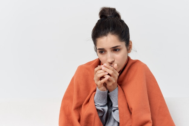 Une femme est assise sur le canapé à la maison recouverte d'une couverture et boit du thé froid