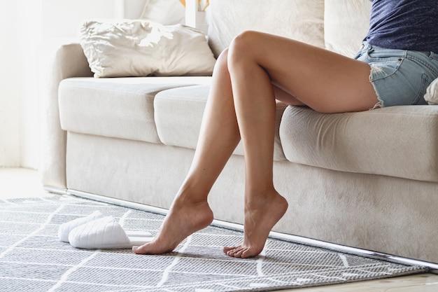La femme est assise sur le canapé et ses jambes sont sans pantoufles sur le tapis