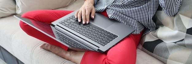 La femme est assise sur le canapé sur ses pieds se trouve un ordinateur portable