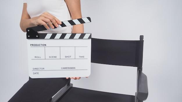La femme est assise sur la chaise et les mains tiennent le clap ou l'ardoise de film. il utilise dans la production vidéo, le cinéma, l'industrie du cinéma sur fond blanc.