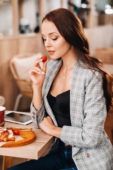 Une femme est assise dans un café et mange des fraises. une fille avec des fraises dans ses mains dans un café.