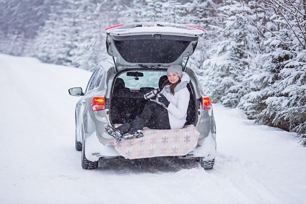Une femme est assise dans le coffre de la voiture et tient une tasse de thé chaud dans les mains. vacances d'hiver, voyage. forêt de neige et route - image