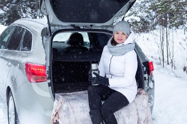Une femme est assise dans le coffre de la voiture et tient une tasse de thé chaud dans les mains. vacances d'hiver, voyage. forêt de neige et route. temps de neige - image
