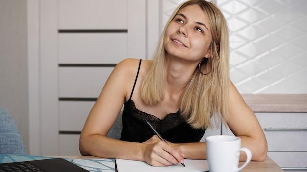Une femme est assise dans une cuisine lumineuse et écrit une lettre ou ses souhaits