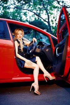Une femme est assise dans sa décapotable rouge avec ses jambes sur la