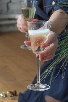 La femme est assise sur un plancher en bois, tient un verre de champagne et sert le deuxième verre au spectateur.