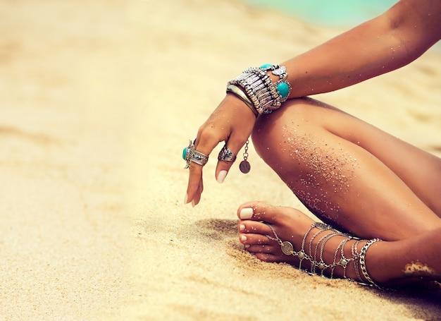 Femme est assise en position détendue sur la plage de sable tropicale parties du corps femme bronzée en position du lotus vêtue de bijoux en argentbracelets et bagues de style boho