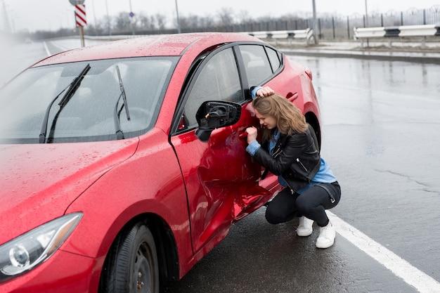 Une femme est assise près d'une voiture cassée après un accident. appeler à l'aide. assurance voiture