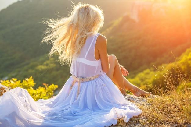Une femme est assise sur un rocher et regarde la belle vue au soleil