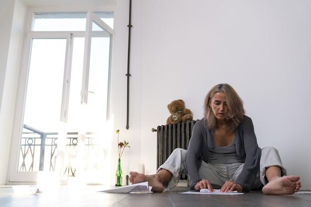 Une femme est assise sur le sol à côté d'une batterie de radiateur et fait un avion en papier