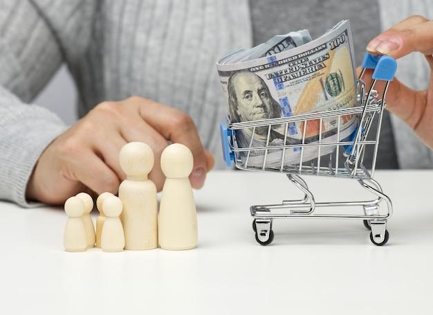 Une femme est assise à une table et un chariot miniature avec des dollars américains. concept d'épargne, de vente, d'impôt