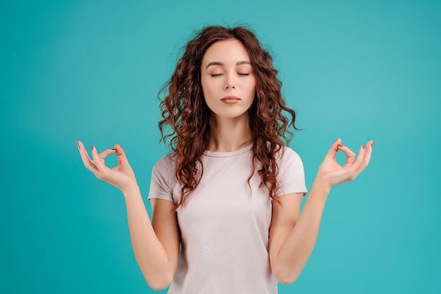 La femme est calme et détendue avec des gestes zen isolés sur fond bleu turquoise