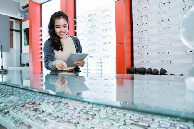 Une femme est dans une clinique ophtalmologique et tient un catalogue de produits de lunettes avec un mur de fenêtre d'affichage de lunettes