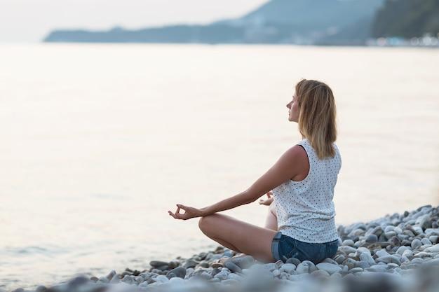 Une femme est engagée dans la méditation du soir au bord de la mer assise dans la position du lotus